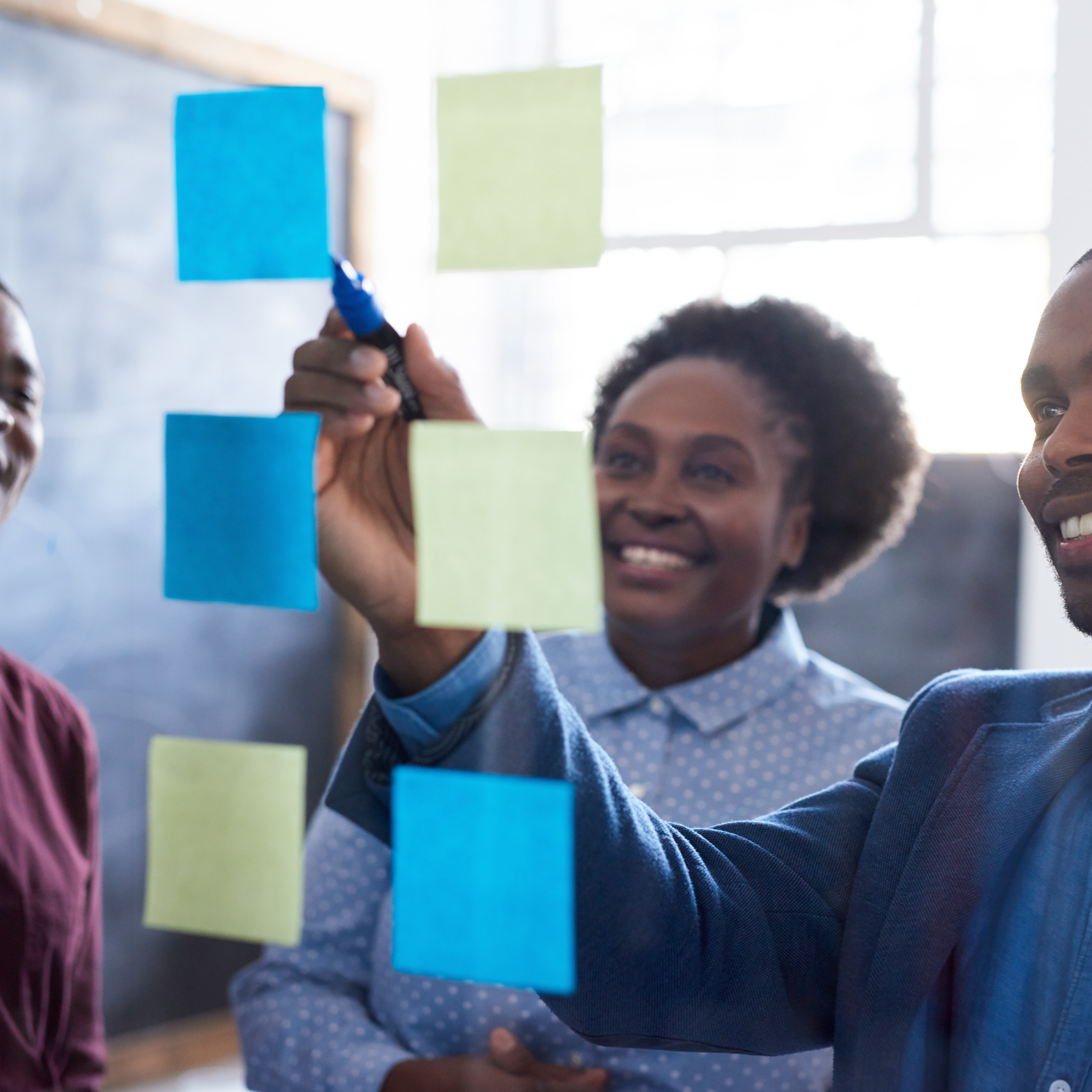 Three casually dressed African work colleagues brainstorming together on a glass wall with sticky notes while standing in a modern office